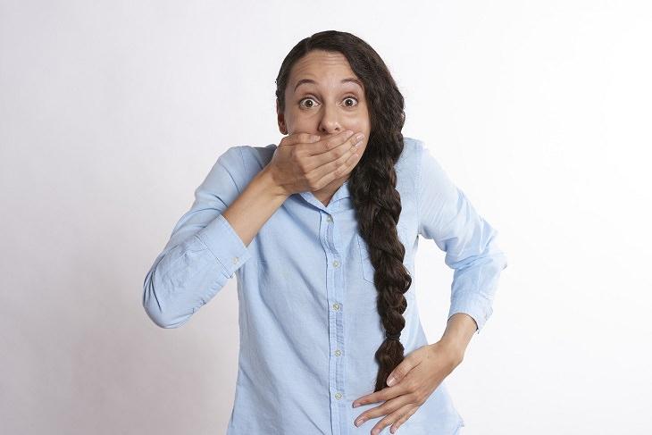 כך תזהו דכאון סמוי ותטפלו בו: אישה פוקחת עיניים לרווחה ושמה את ידה על הפה ועל הבטן