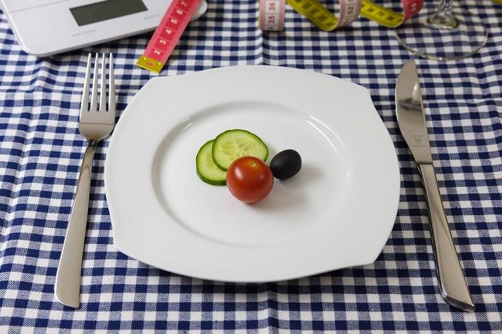 """סימנים מוקדמים לדלקות מפרקים: צלחת עם מספר חתיכות של ירקות מונחת על שולחן לצד סכו""""ם"""