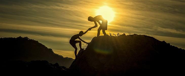 משפטים שצריך להגיד יותר בעבודה: צללית של אדם עוזר לאיש אחר לטפס על הר