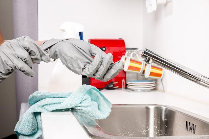 טעויות נפוצות שאתם עושים בניקיון הבית: אדם עוסק בניקיון עם כפפות על ידיו