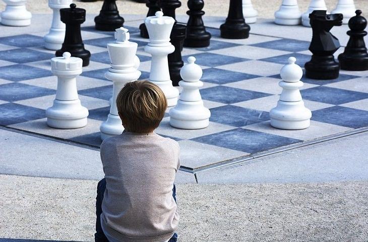 טריקים פסיכולוגיים להורים: ילד יושב מול משטח שח-מט גדול