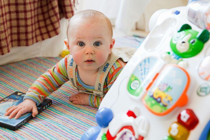 טיפים לסיוע להתפתחות ולמידה של תינוקות: תינוק שוכב על בטנו ליד צעצוע