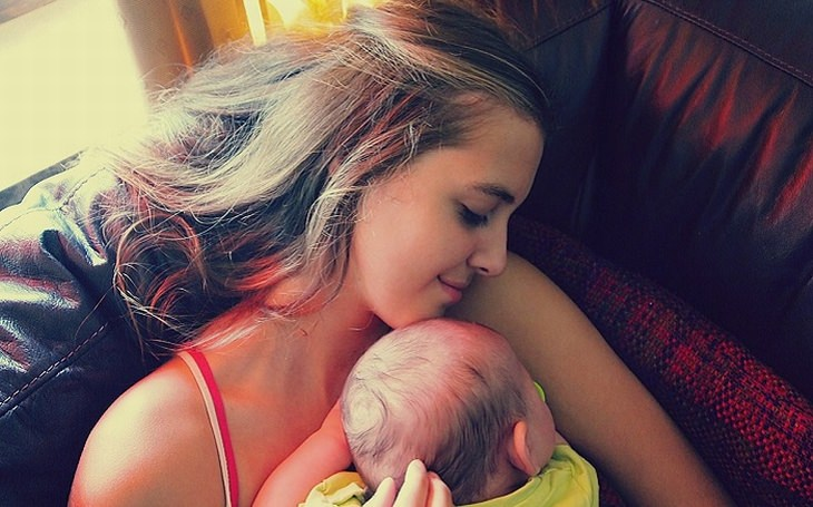 טיפים לסיוע להתפתחות ולמידה של תינוקות: אם שוכבת על ספה כשהתינוק שלה בזרועותיה