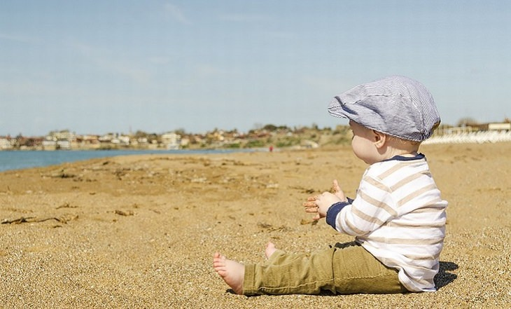 טיפים לסיוע להתפתחות ולמידה של תינוקות: תינוק יושב על החול בחוף הים