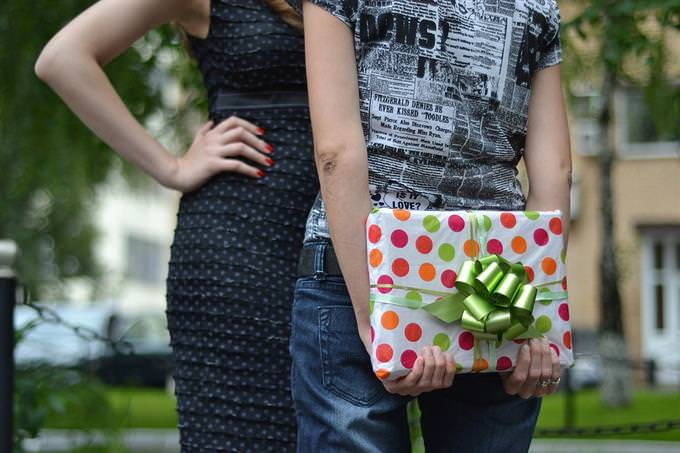מבחן חברות: אישה מחזיקה מתנה עטופה מאחורי הגב