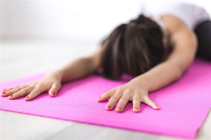 נשימה מודעת: אישה נמתחת קדימה על מזרן יוגה
