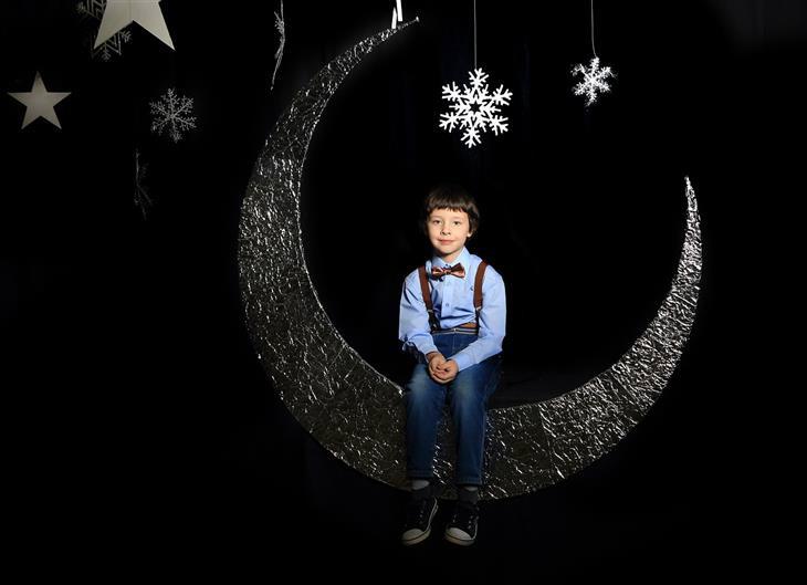 סימנים לאוטיזם: ילד יושב על תפאורה בצורת ירח