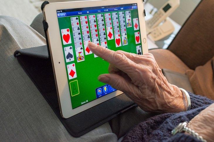 מחקר על הקשר בין בריאות וקשר משפחתי בגיל הזהב: ידי אישה מבוגרת נוגעות במסך של מחשב לוח עם משחק קלפים