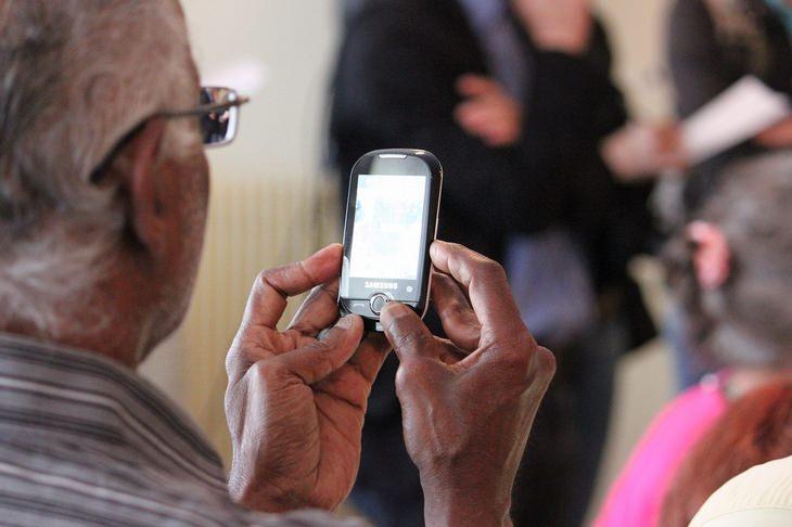 מחקר על הקשר בין בריאות וקשר משפחתי בגיל הזהב: אדם מבוגר מחזיק טלפון נייד בידו