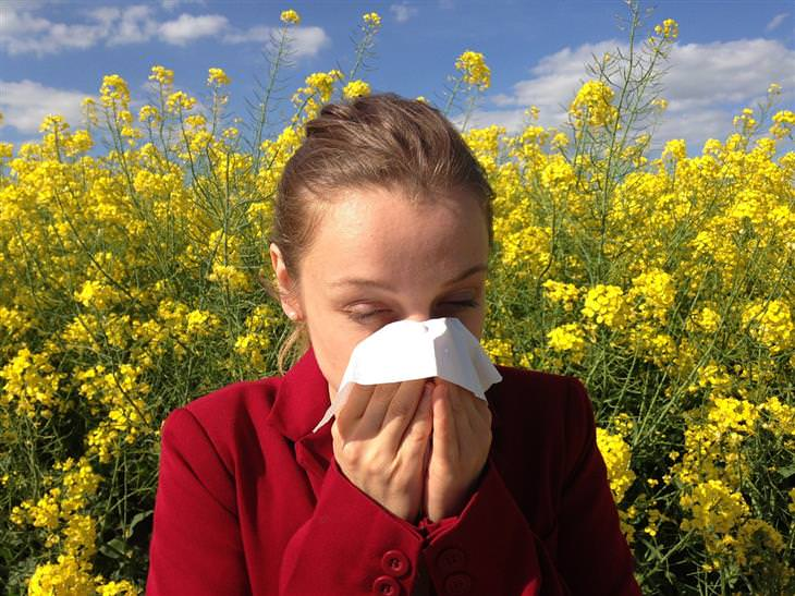 טיפול בנזלת אלרגית: אישה מקנחת את האף בשדה פרחוני