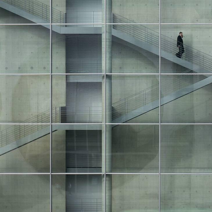 תמונות מדהימות מתחרות צילום של הסמיתסוניאן: איש יורד במדרגות בבניין בעל קירות זכוכית עם משבצות סימטריות ביחס למדרגות