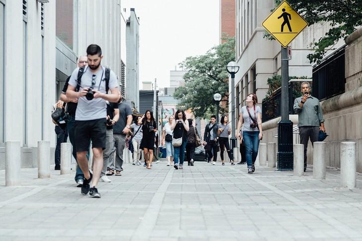 חוק 5/25 של וורן באפט: אנשים צועדים ברחוב ומתעסקים בטלפון הסלולרי שלהם