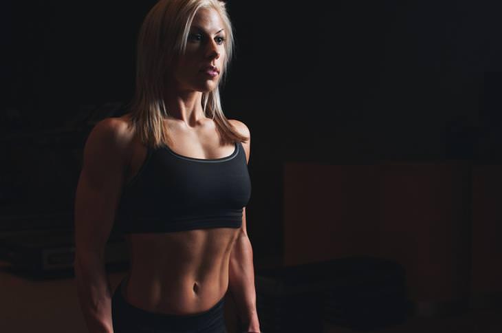 רצף תרגילי כושר לחיזוק וחיטוב הזרועות ושרירי הבטן: אישה חטובה בבגדי התעמלות