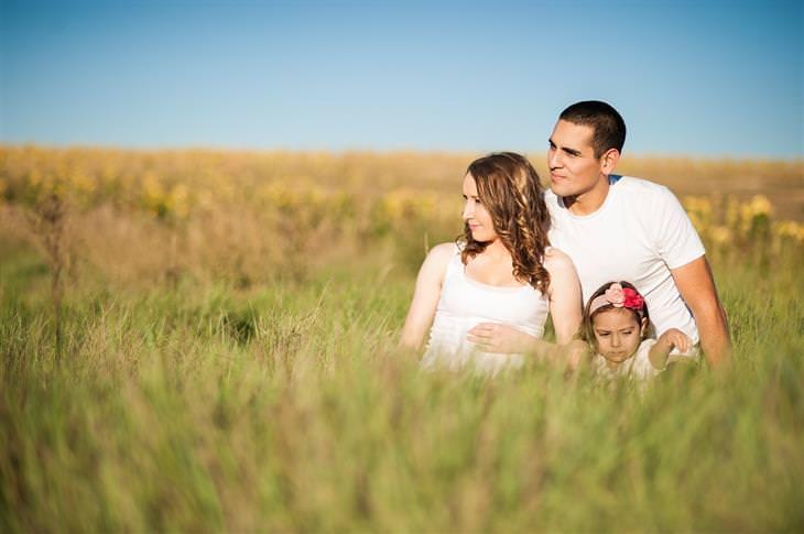 משברים נפוצים בחיי הנישואים: גבר, אישה וילדה יושבים בשדה פרחוני