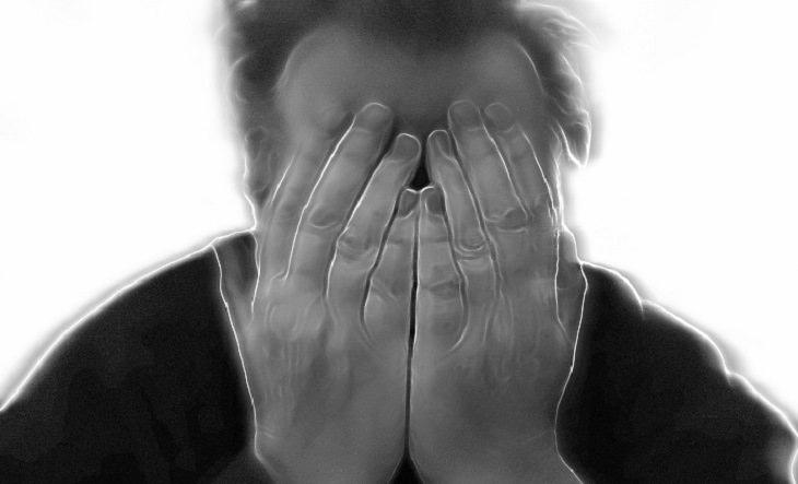 כיצד ניתן לטפל בסחרחורת: אדם תופס את פניו בכפות ידיו
