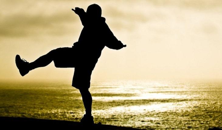 כיצד ניתן לטפל בסחרחורת: אדם מנסה לייצב את שיוויו משקלו על רקע חוף הים