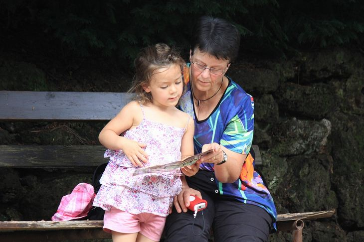 ברכה לסבא וסבתא: סבתא קוראת עם נכדתה בפארק