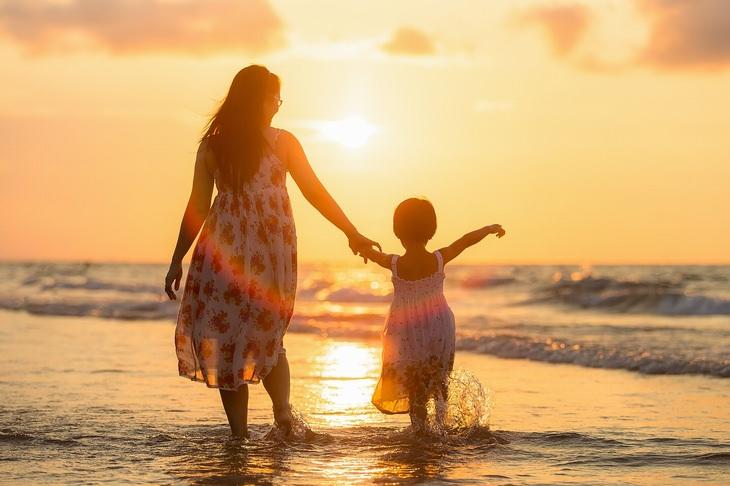 עצות לגידול ילדים מאושרים: אם ובתה צועדות בים על רקע שקיעה