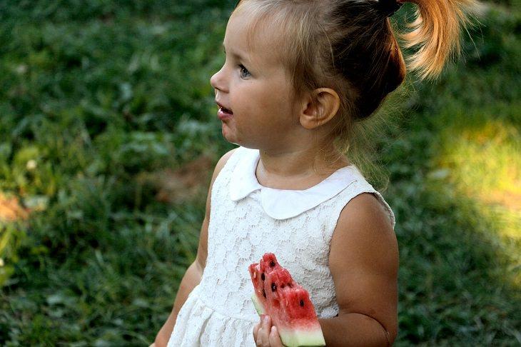 מחקר על תזונה ובריאות נפשית בקרב ילדים: ילדה אוחזת בפרוסת אבטיח