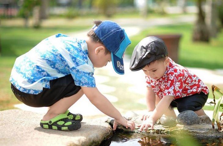 עובדות מעניינות: שני ילדים קטנים משחקים ליד שלולית מים