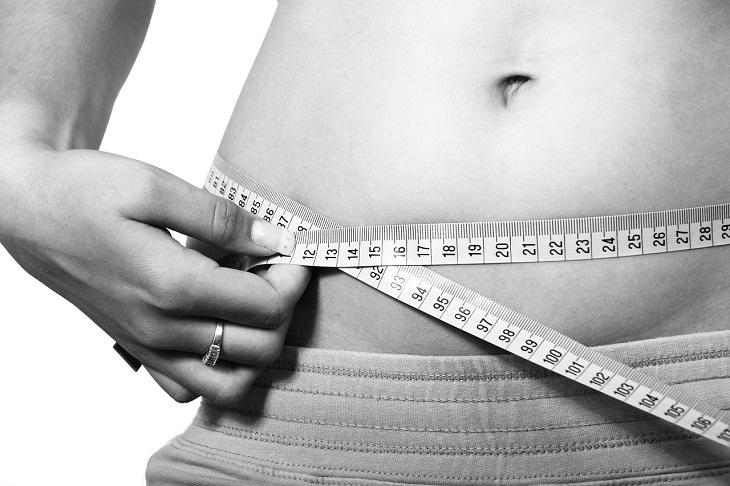 הדברים שתזונאים רוצים שתדעו על ירידה במשקל: אישה מקיפה את בטנה בסרט מדידה