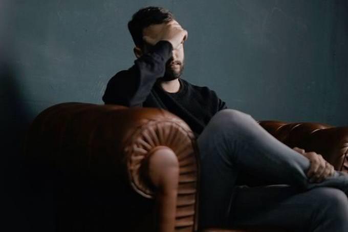 בחן את עצמך - מוח גברי או נשי: בחור מחזיק את פניו עם ידו וחושב