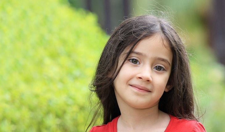 התמודדות של הורה מוחצן לילד מופנם: ילדה מחייכת בביישנות