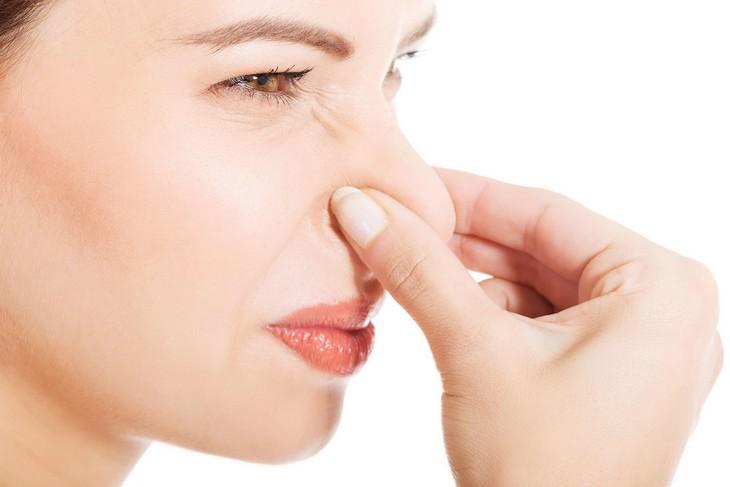 סיבות לכאבי ראש: אישה אוטמת את אפה