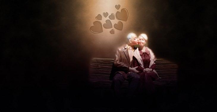 מה קורה במוח בזמן התאהבות: שתי בובות בדמות זוג מבוגר יושבות על הספסל, כשבובת הגבר נושקת לבובת האישה