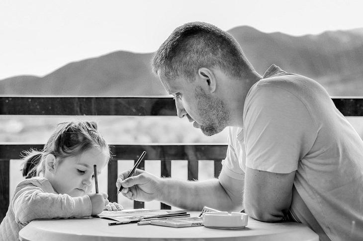 4 שלבי גידול ילדים על פי הטיבטים: אב יושב עם ילדתו ועוזר לה במילוי דפי עבודה