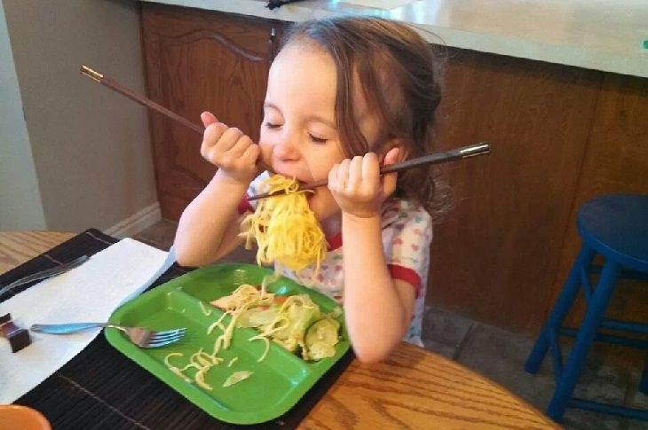 חוויות ראשונות: ילדה מנסה לאכול עם מקלות אכילה