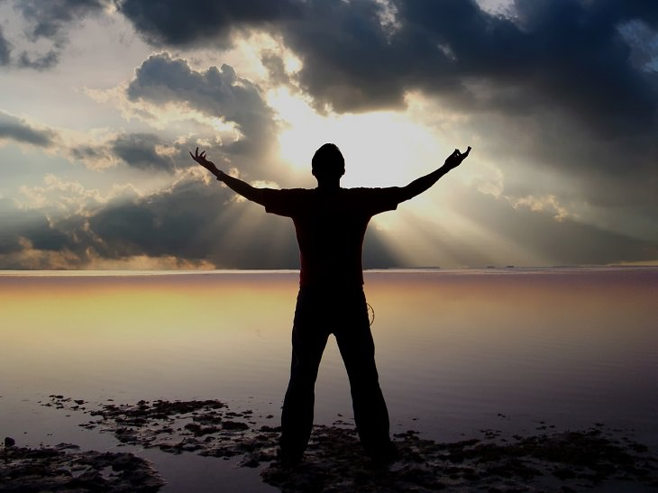 טיפים להשבת האושר לחיים: אדם עומד אל מול השקיעה ופותח את זרועותיו