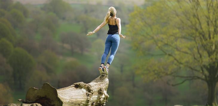 דברים מעוררי מחשבה שישנו את חייכם: אישה עומדת על בול עץ ומותחת את גופה מעלה