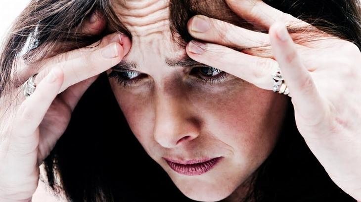 משקה טבעי לטיפול בכאבי ראש: אישה מחזיקה את ראשה בידיה