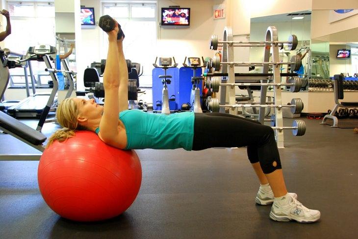 תרגילים לחיזוק הגב ושרירים אחוריים: אישה מבצעת תרגיל לחיצות חזה על כדור התעמלות