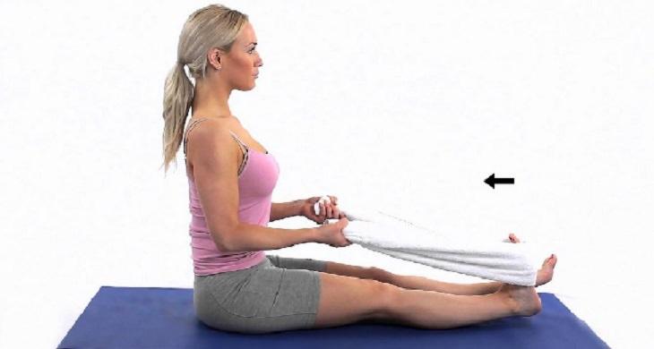 תרגילי גמישות: אישה מבצעת את תרגיל מתיחת המגבת בישיבה