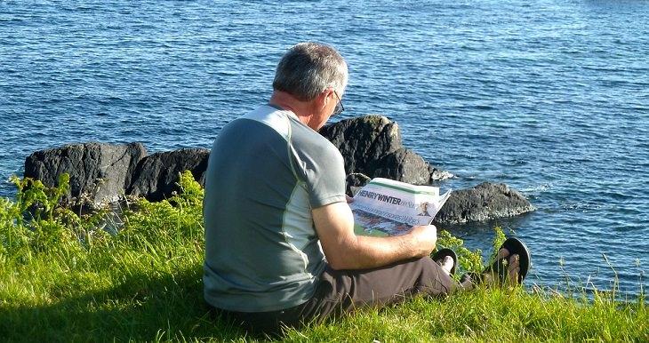 שחיקת סחוסים: גבר מבוגר נח על שפת המים וקורא עיתון
