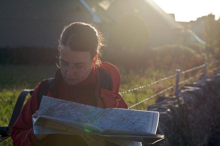 כללי בטיחות בטיולים: אישה מתבוננת במפת דרכים