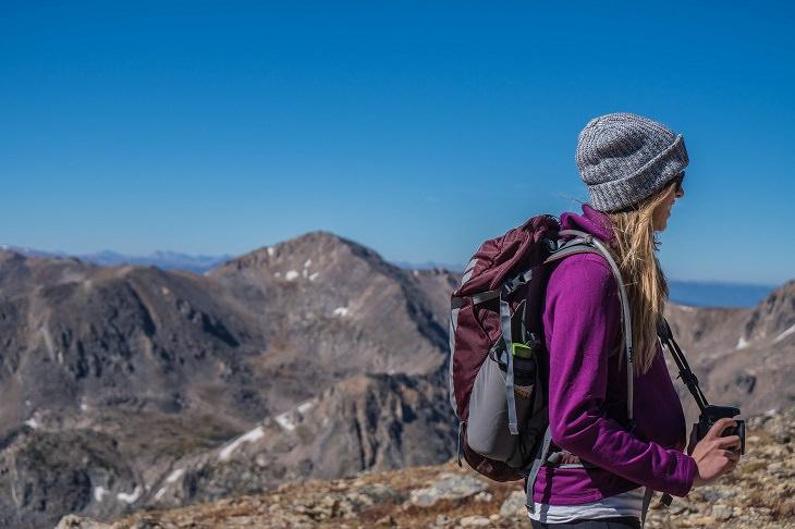 כללי בטיחות בטיולים: אישה בטיול, מצוידת בתיק, כובע, משקפי שמש וביגוד ארוך