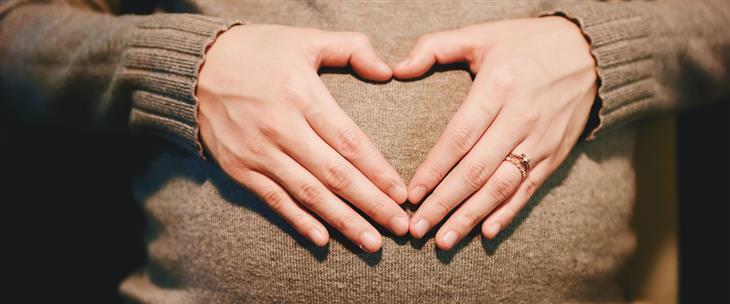 רשימת מטלות להיריון: אישה מניחה את ידיה על בטנה ההרה בצורת לב