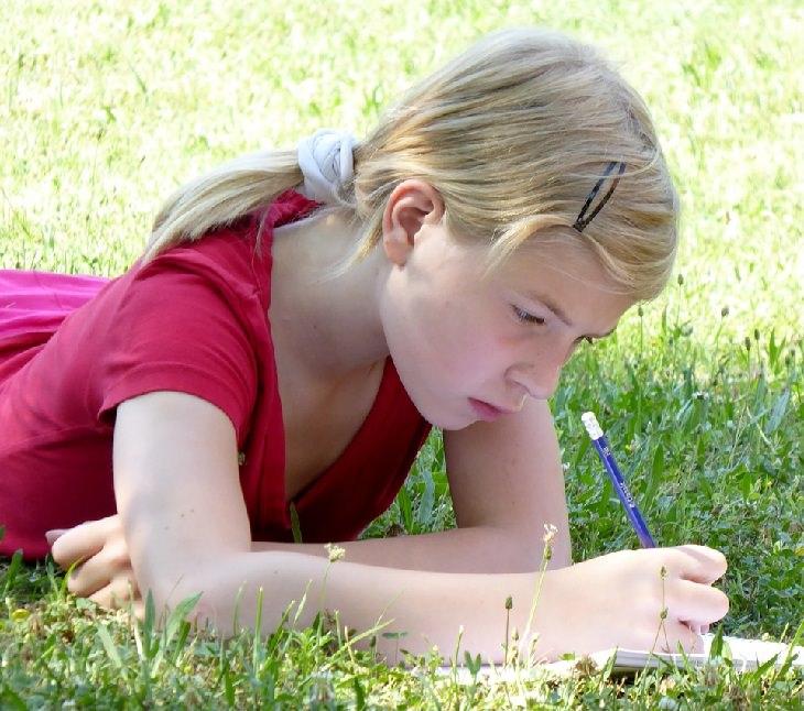 מסרים שגויים בסרטי דיסני: ילדה כותבת בזמן שהיא שוכבת על דשא