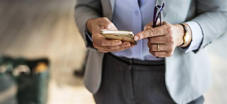 הזמנים שבהם מומלץ שלא להשתמש בסמארטפון: אישה בחליפה משתמש בסמארטפון