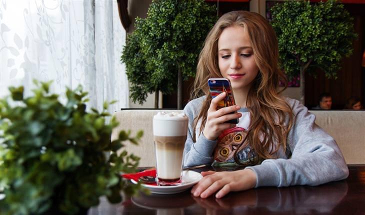 הזמנים שבהם מומלץ שלא להשתמש בסמארטפון: אישה מסתכלת בסמארטפון