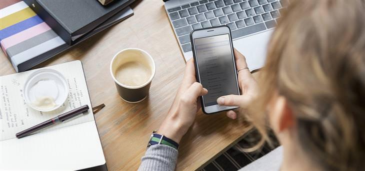 הזמנים שבהם מומלץ שלא להשתמש בסמארטפון: אישה משתמשת בסמארטפון