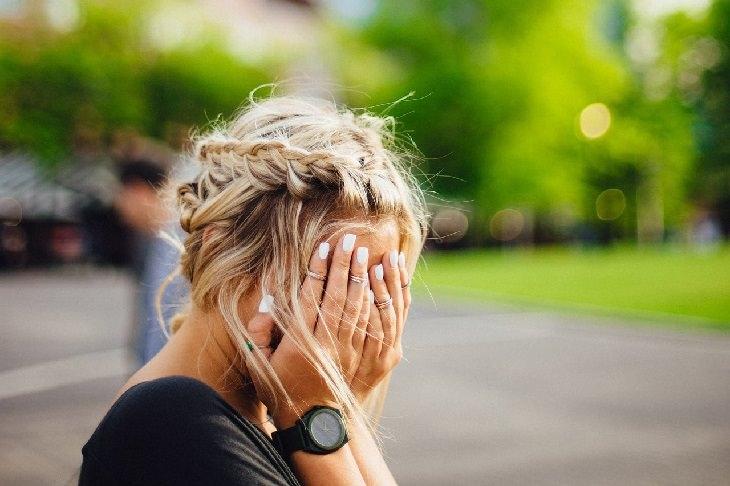 תופעות לוואי של הריון: אישה מסתריה את פניה בבושה