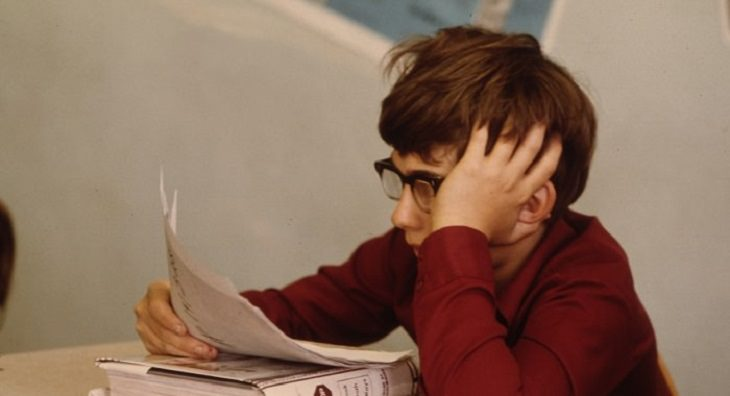 הפרעות קשב וריכוז: ילד מתבונן בדף נייר כשידו על ראשו