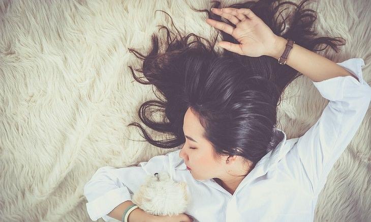 תוסף B12:  אישה פזורת שיער שוכבת על מיטה על כלב קטן