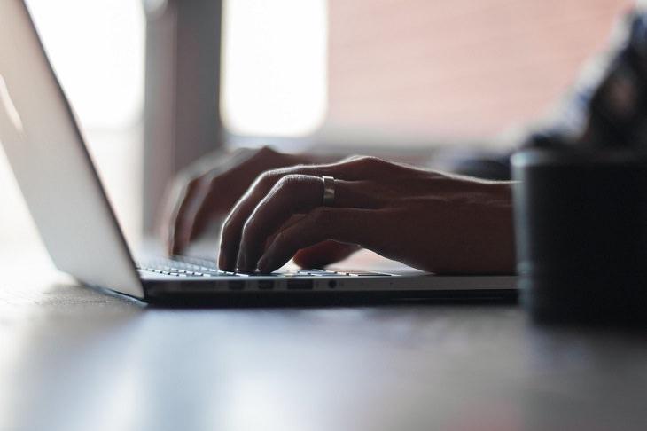 תכונות אופי של בעלי אישיות חזקה: ידיים של אדם עובדות על מקלדת מחשב נייד
