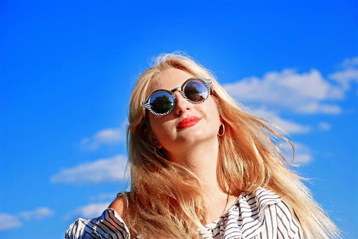 כל מה שצריך לדעת על ספיגת ויטמין D מהשמש: אישה עם משקפי שמש ומעלה שמים כחולים