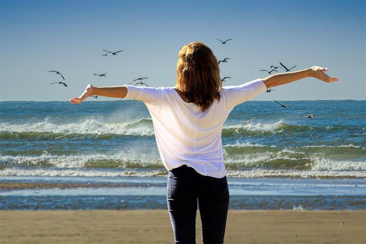 כל מה שצריך לדעת על ספיגת ויטמין D מהשמש: אישה מרימה את ידיה לאוויר על שפת הים
